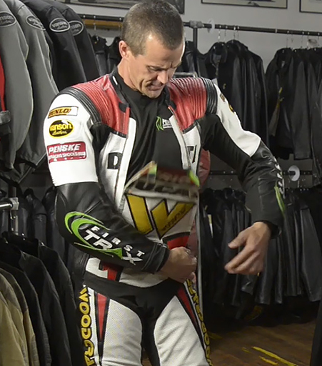 Eric Wood demonstrates Vanson's dual zippered front panel on his Air-Pro air bag racing suit